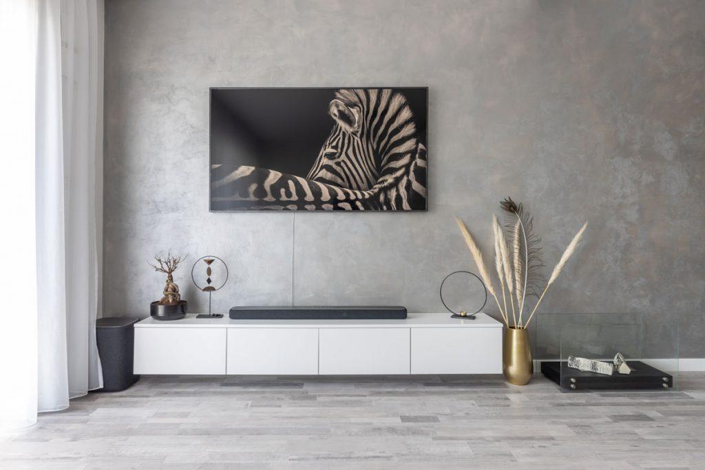 minimalistický priestor televíznej steny s jednoduchými závesnými bielymi skrinkami a sivou omietkou s hnedozlatými odleskami