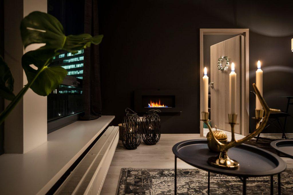 glamour interiér obývačky s biokozubom, miestnosť je zariadená vo farebnej kombinácii čiernej a zlatej