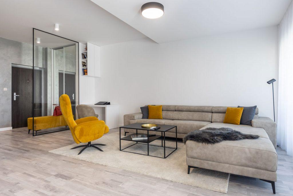 svetlý priestor minimalistickej obývačky v neutrálnych sivo-hnedých farbách s akcentom na žltom kresle a sklenou stenou, ktorá oddeľuje chodbu od zvyšného priestoru