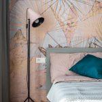 detail spálne so sivou posteľou a veľkometrážnou tapetou s rastlinným motívom vo vzorovom byte Kolísky