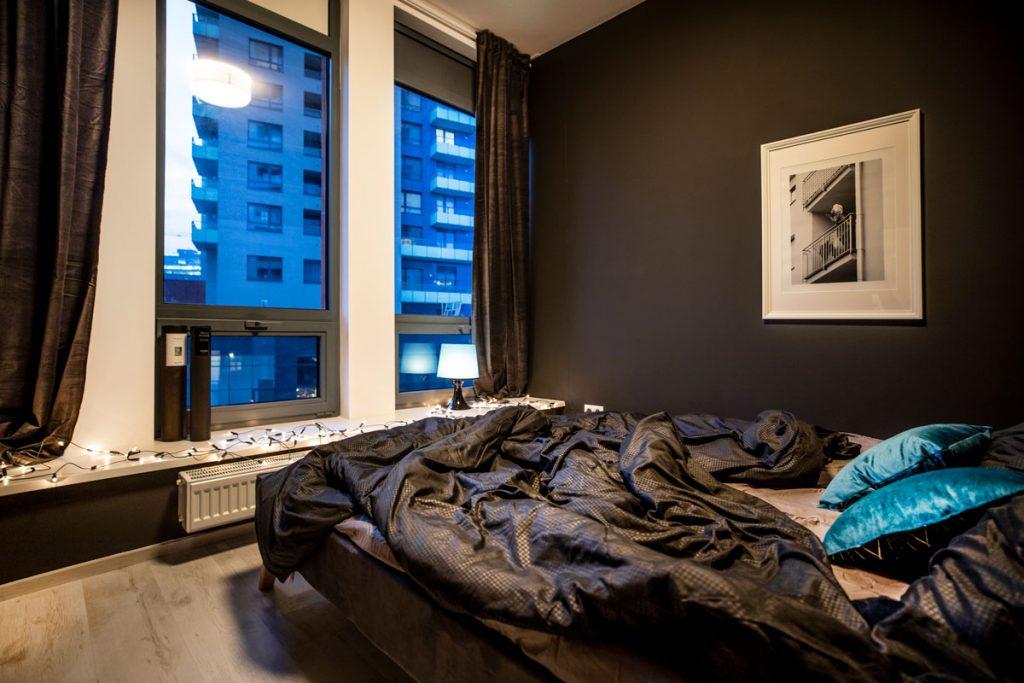 elegantná spálňa s čiernou stenou a posteľou netradične umiestnenou oproti oknu s výhľadom