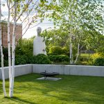 minimalistická záhrada s brezami, nízkym múrikom, ktorý oddeľuje zeleň od plochy na grilovanie a zároveň slúži ako sedenie a s nadrozmernou sochou