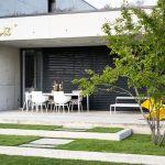 vstup do záhrady zo strany od domu, ktorý postupne prechádza z betónovej terasy do nášľapných betónových dosiek lemovaných koseným trávnikom