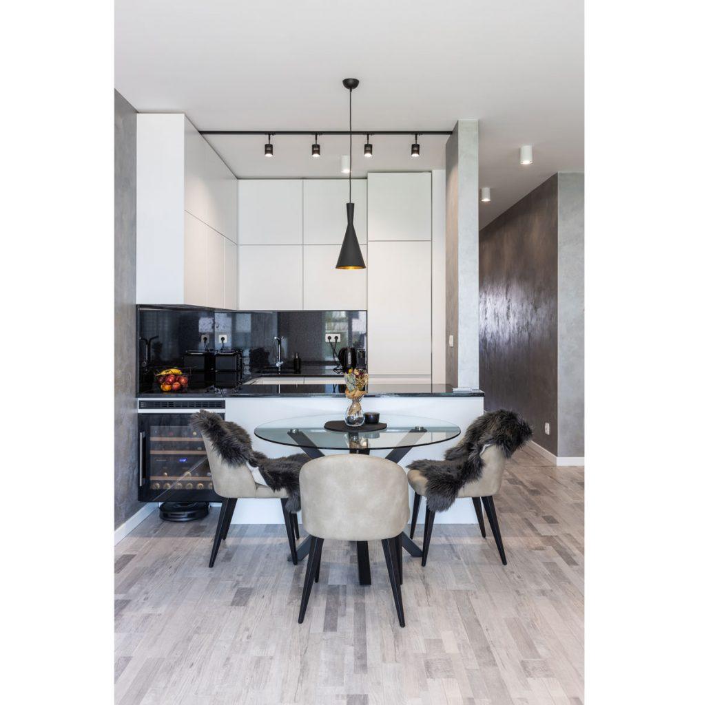 Minimalistická kuchyňa v tvare U s čiernou lesklou doskou z kameňa a jedálenským stolom s čalúnenými stoličkami