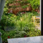Pohľad z interiéru ateliéru Partero do záhrady s pestrou neformálnou výsadbou a terasou so sedením