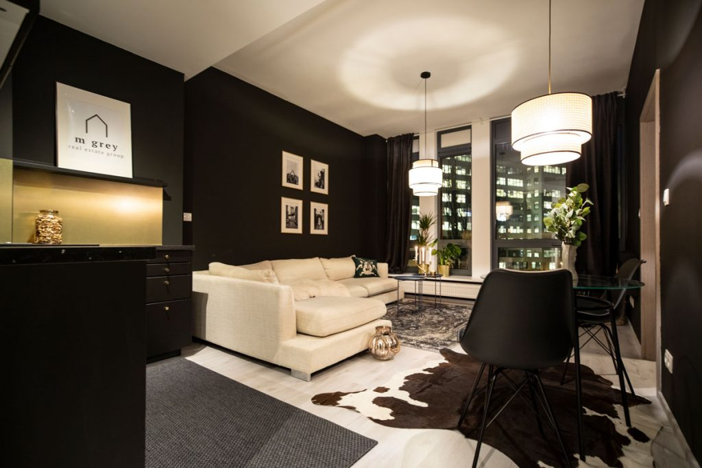 Elegantný interiér obývačka spojenej s kuchyňou, v ktorom dominuje kombinácia čiernej a zlatej, luxusné materiály a kožušiny