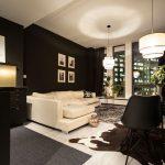 Elegantný interiér obývačky spojenej s kuchyňou, v ktorom dominuje kombinácia čiernej a zlatej, luxusné materiály a kožušiny
