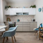 Jednoduchá kuchynská linka v kombinácii bielej a hnedej, jedálenský stôl s čalúnenou svetlomodrou stoličkou a bielymi stoličkami a starodávny pojazdný servírovací stolík