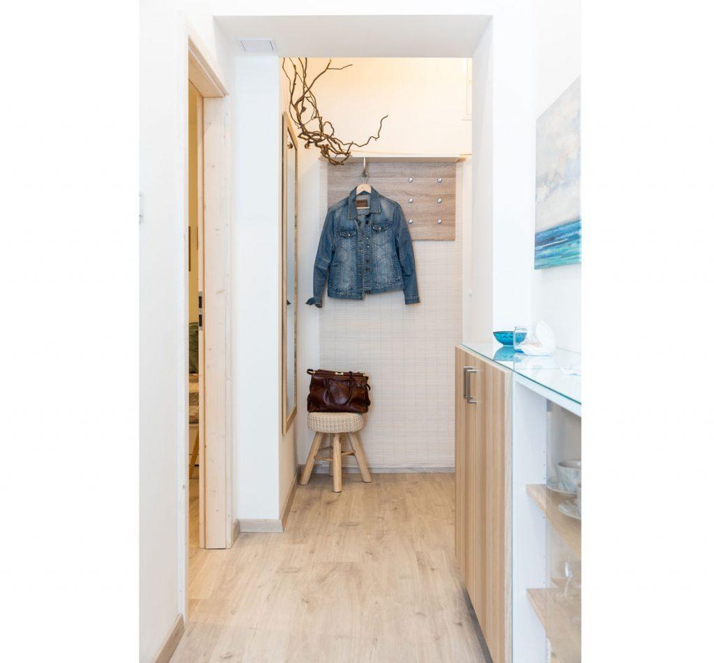 jednoducho zariadená chodba bez vstavaných skríň v kombinácii bielej a svetlého dreva