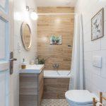kúpeľňa v kombinácii bielej s hnedým obkladom, v škandinávskom štýle, a so zrenovovaným okrúhlym starožitným zrkadlom