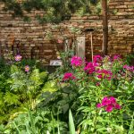 záhradná časť s náradím a kompostérom čiastočne ukrytá pestrou výsadbou