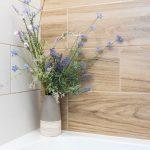 detail kúpeľne s kyticou umelých kvetov v rohu vane