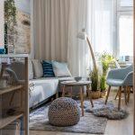 Interiér obývačky v stredomorskom a škandinávskom štýle, ladený vo svetlých farbách a tón v tóne, s ručne vyrábanými dekoráciami, izbovými rastlinami, sivou sedačkou a kreslom