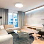 štvorizbový vzorový byt v Kolískach: Neutrálne ladená obývačka so zarámovanou tapetou s motívom krajinárskej scenérie a podsvietenou LED svetlami