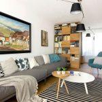 zrekonštruovaná obývačka v staršom rodinnom dome s dizajnovým retro kreslom značky Pedrali a sivou sedačkou značky Bonaldo, okrúhlymi stolíkmi a knižnicou, za ktorou je pracovňa