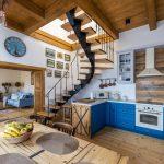 Interiér Domu na hradbách v Levoči: pohľad do kuchyne s modrou linkou s jedálenským stolom, točitým schodiskom na poschodie a obývačkou zariadenou kombináciou rôznych štýlov