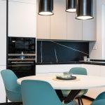 štvorizbový vzorový byt v Kolískach: kuchyňa a stolovacia časť v neutrálnych farbách s retro čiernym lustrom a tyrkysovými stoličkami