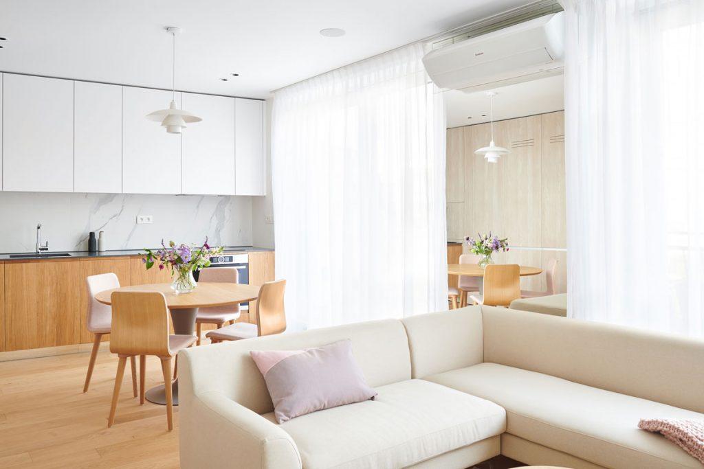interiér obývačka prepojenej s kuchyňou v jemných pastelových a svetlých farbách a v minimalistickom škandinávskom dizajne, s nadrozmerným zrkadlom, ktoré opticky zväčšuje miestnosť