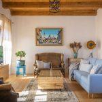 Obývačka v Dome na hradbách zariadená v kombinácii viacerých štýlov, s koženými vintage kreslami a modernou svetlomodrou sedačkou, s obrazom zarámovaným v recyklovanom okennom ráme z pôvodného domu