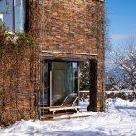 fasáda rodinného domu s kamenným obkladom pokrytým zimolezom a malou terasou s lehátkom