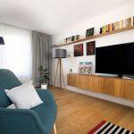 časť obývačky v retro a škandinávskom štýle so závesnou skrinkou s televíziou, otvorenou policou s knihami, modrým retro kreslom