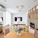 minimalistická obývačka s bielou sedačkou, knižnicou po celej bočnej stene a domácim kinom, ktorého reproduktory sú zabudované do steny a stropu