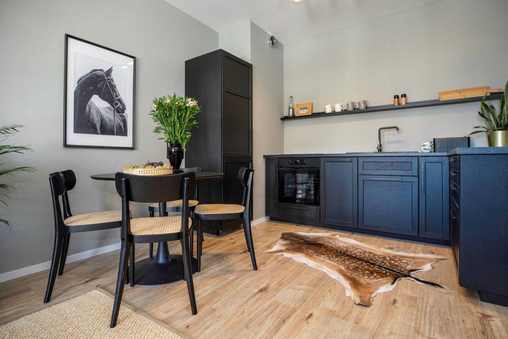 pánsky interiér kuchyne s čiernym nábytkom zladeným so svetlohnedou drevenou podlahou a svetlými sedákmi na stoličkách