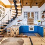 kuchyňa v Dome na hradbách s výraznou modrou kuchynskou linkou umiestnenou pod točitým schodiskom