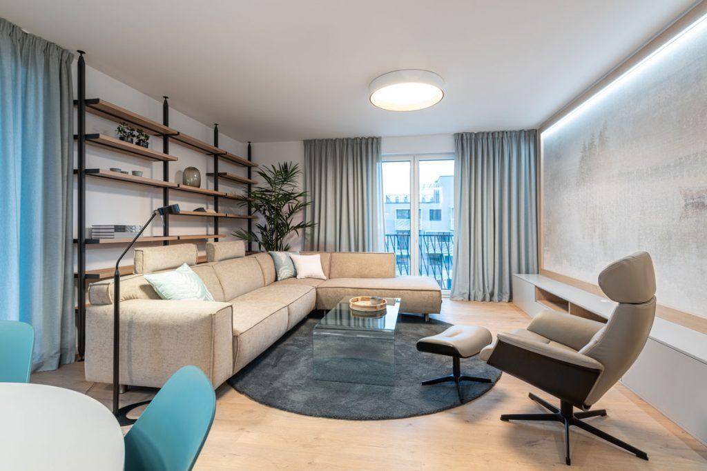 štvorizbový vzorový byt v Kolískach: obývačka v neutrálnych farbách, s otvoreným regálom a tapetou s krajinárskym motívom zarámovanou v dubovom ráme a s LED podsvietením