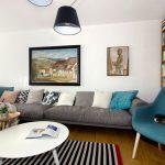 zrekonštruovaná obývačka v staršom rodinnom dome v retro a modernom štýle so sivou pohovkou, modrým kreslom, obrazmi a knižnicou