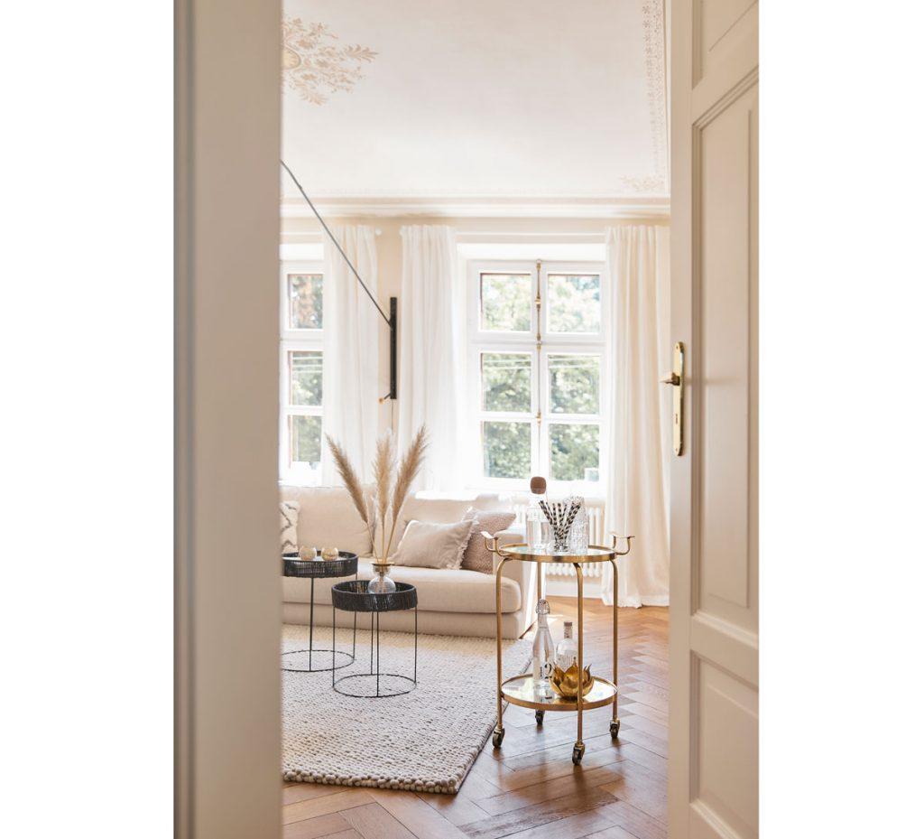 Prírodná obývačka v krémových odtieňoch, s okrúhlymi stolíkmi a pampou vo váze