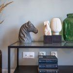 detail sklenenej poličky s knihami, soškou konskej hlavy a ľudskej tváre a vázou z farebného skla s okrasnými trávami