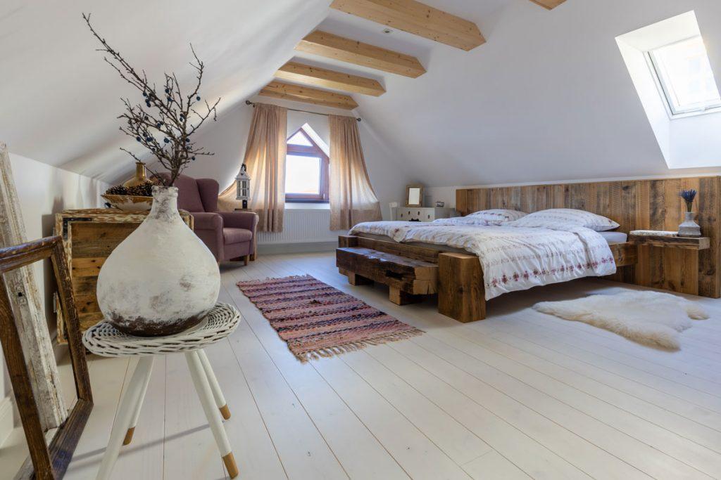 podkrovná spálňa v Dome na hradbách v severskom štýle s priznanými stropnými trámami, obnovenou podlahou natretou na bielo a masívnou drevenou ručne vyrobenou posteľou
