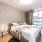 štvorizbový vzorový byt v Kolískach: spálňa v jemnej palete farieb s kontrastom v drevenej podlahe, s tapetou s motívom Zlodeja jahôd