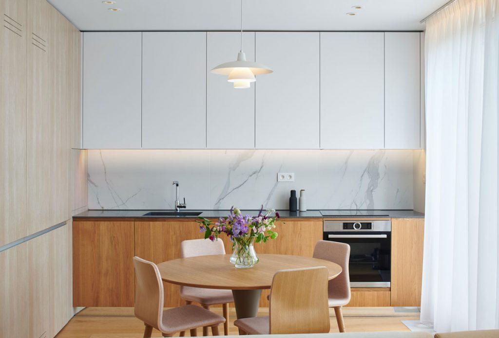 kuchyňa s jedálňou: kuchynská minimalistická stena, ktorá ukrýva potraviny a spotrebiče, s osvetlenou linkou a náladovým podsvietením záclon