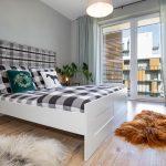spálňa v pánskom štýle s čalúnenou károvanou posteľou, kožušinou v škoricovej farbe a svetlohnedou podlahou