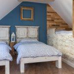 spálňa s tmavou podlahou a ručne vyrobenými bielymi drevenými posteľami vo vidieckom štýle a lôžkom umiestnením pod šikminou strechy