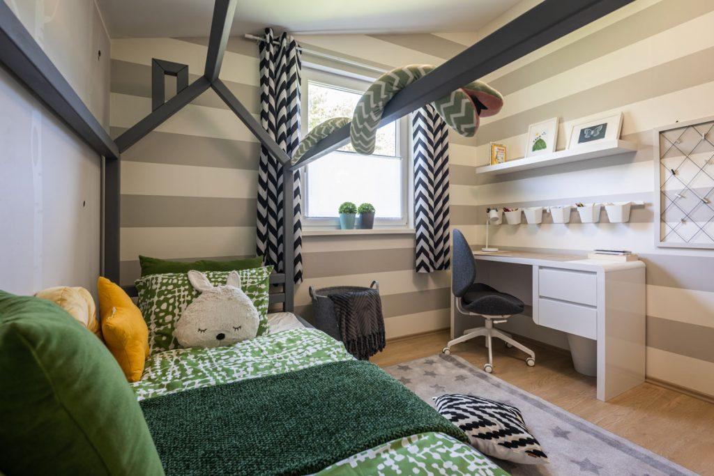 detská izba v neutrálnych odtieňoch a výrazným zeleným posteľným prádlom v posteli v tvare domčeka