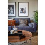 detail obývačky v pánskom štýle s farebnou čalúnenou sedačkou, s vankúšmi v škoricovej farbe a so vzorom kohútej stopy, s okrúhlym stolíkom a obrazmi s motívom koní
