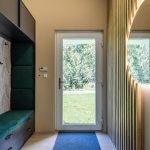 chodba v dome s výklenkom s úložnými priestormi a zamatovým poťahom, tapetou so vzorom listov, obkladom z latiek a okrúhlym podsvieteným zrkadlom