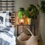 detail spálne s károvanou posteľou, zelenými rastlinami, nočnou lampou a prírodným odkladacím košom