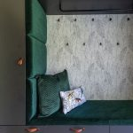 čierne úložné priestory v chodbe, ktoré vytvárajú výklenok na sedenie z tmavozeleného zamatu, s tapetou so vzorom listov