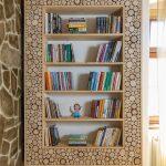 ručne vyrobená nástenná knižnica, ktorej rám je vyplnený odpadovými odrezkami z konárov stromov