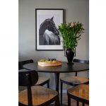 detail jedálenského stola v čiernej farbe, s čiernymi stoličkami s vypletaným hnedým sedákom, vázou s kvetmi a zarámovaným plagátom koňa