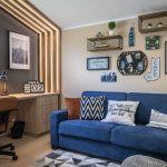 pracovňa spojená s hosťovskou izbou s modrým gaučom, pracovným stolom a obkladom z latiek podsvietených LED svetlom