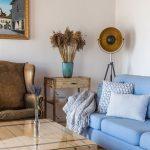 detail obývačky v Dome na hradbách s pôvodnou drevenou podlahou, ručne vyrobeným dreveným stolíkom, koženým kreslom a svetlomodrou modernou sedačkou