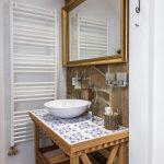 kúpeľňa v Dome na hradbách vo vidieckom štýle s kamenným obkladom na stene a zrkadlom osadeným v starožitnom ráme