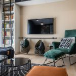 priestor obývačky s televízorom, pod ktorým je garniža s úložnými košmi, so zeleným zamatovým kreslom a bielou knižnicou, z ktorej plynule prechádzajú úložné priestory popod strop