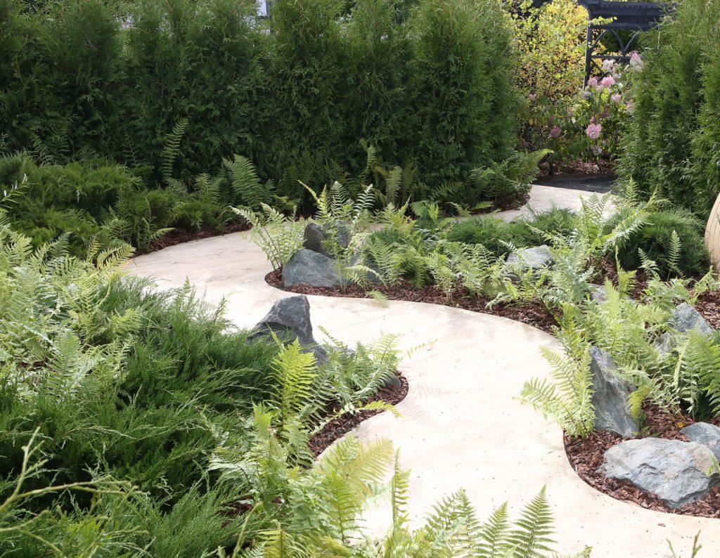 Ako vyriešiť malú záhradu: Záhrada so zeleňou a oblúkovito riešeným chodníkom