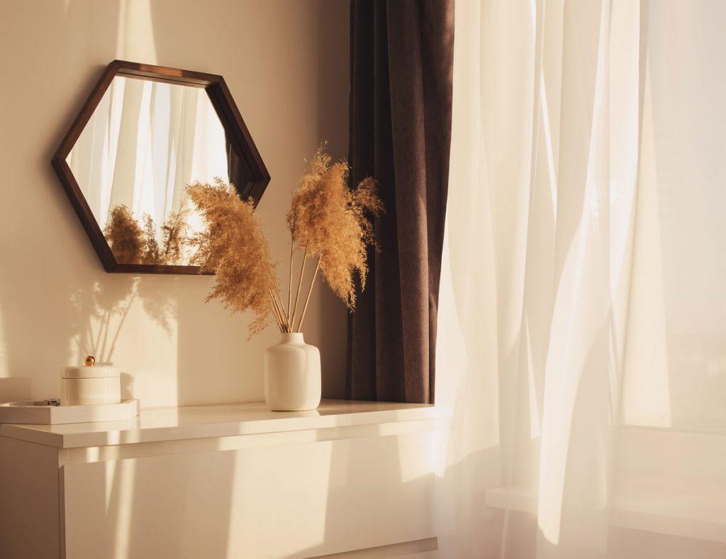 Interiér s bielou vázou, v ktorej je okrasná tráva pampa